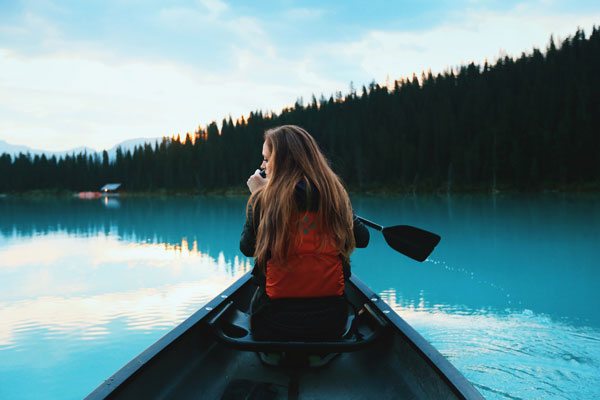 woman in canoe on blue water looking for mindfulness classes and coaching in seattle for adults and teens with anxiety depression stress trauma shame recovery