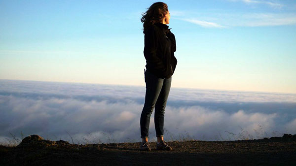 woman looking over clouds and horizon for mindfulness classes and coaching in seattle for adults and teens with anxiety depression stress trauma