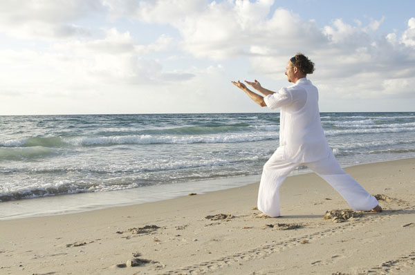 man on beach doing qi gong meditation classes and coaching in seattle for adults and teens with anxiety depression stress trauma